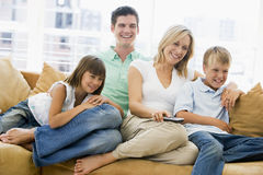 Family sitting in living room with remote control Stock Photo