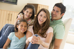 Family sitting in living room smiling stock photo