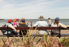Family sitting on long wooden public bench  looking out to sea. Llandudno, North Wales- 17th May 2014 : Family sitting on long wooden public bench  looking out Royalty Free Stock Photo
