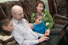 Family sitting look at laptop screen Stock Images