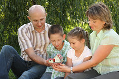 Family is sitting and looking at wendy house. Family in early fall park. father, mother, little boy and girl is sitting on the grass near osier and looking at Royalty Free Stock Photos