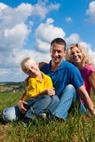 Family sitting on meadow Royalty Free Stock Photography