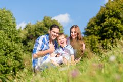 Family sitting on meadow with child waving hands Stock Photo