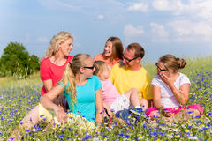 Family sitting on meadow in flowers Stock Photos