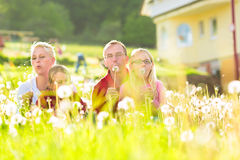 Family sitting in meadow in front of home Stock Photography