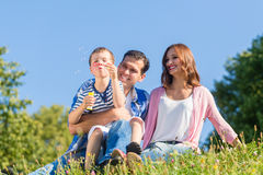 Family sitting on meadow playing with soap bubbles Royalty Free Stock Images