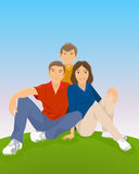 Family sitting in meadow Stock Photo
