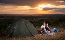 Family sitting near camp tent on the hill stock image