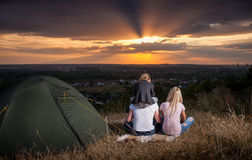 Family sitting near camp tent on the hill stock photos