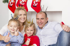 Family sitting near the Christmas fireplace Royalty Free Stock Photography
