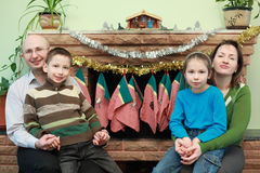 Family sitting near fireplace, Christmas ornaments Stock Photography