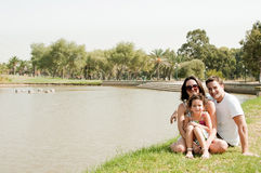 Family sitting near the lake. Young couple embracing and enjoying with young daughter in the park stock photos
