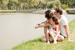 Family sitting near the lake. Young couple embracing and enjoying with young daughter in the park stock photography