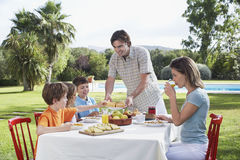 Family Sitting At Outdoor Breakfast Table. Couple with three children sitting at breakfast table outdoors Royalty Free Stock Photos