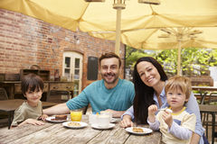 Family Sitting At Outdoor Cafe Table Having Lunch Stock Images
