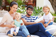 Family Sitting Outdoors In Garden At Home Together Stock Image