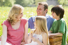 Family sitting outdoors with picnic basket smiling Royalty Free Stock Photos