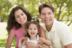Family sitting outdoors smiling Stock Image