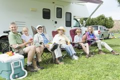 Family Sitting Outside RV Home. Portrait of happy three generational family sitting outside RV home Stock Photography