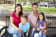 Family Sitting On Park Bench Together Royalty Free Stock Image