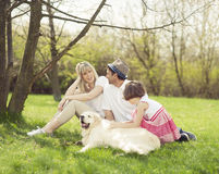 Family sitting in park with dog Stock Photography