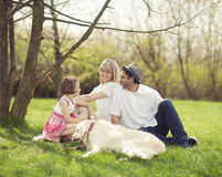 Family sitting in park with dog Royalty Free Stock Photos