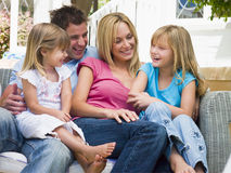 Family sitting on patio smiling Stock Photo