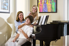Family sitting on piano bench, mother teasing son Stock Photo