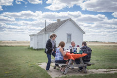Family sitting at a picnic table having lunch. Royalty Free Stock Photos