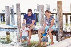 Family sitting on the pier, above water, sunny summer Royalty Free Stock Photography