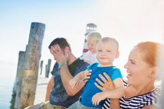Family sitting on the pier, lighthouse, sunny summer day Stock Images