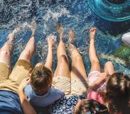 Family sitting by the pool royalty free stock image