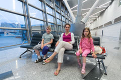 A family  sitting in recreation area in the airport. A family of three sitting in a recreation area in the airport  and waiting for boarding Stock Photos