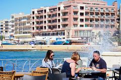 Family at a waterfront restaurant, Marsalforn, Gozo. Family sitting at a restaurant table along the waterfront with the beach and town to the rear and waves Stock Image