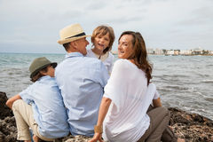 Family sitting on rock and watching the ocean Stock Photos