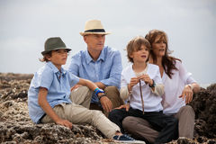 Family sitting on rock and watching the ocean Royalty Free Stock Photography