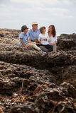 Family sitting on rock and watching the ocean Stock Images