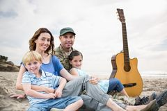 family sitting on sand with a guitar against beach background stock photography