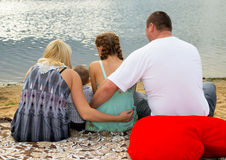 Family sitting by the sea Stock Photos