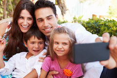 Family Sitting On Seat In Garden At Home Taking Selfie Stock Photo