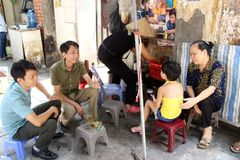 Family sitting on street in Hanoi, Vietnam. Family sitting on side of the street in Hanoi, Vietnam, talking and smiling Royalty Free Stock Photography