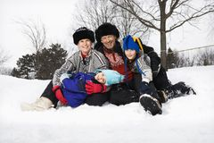 Family sitting in snow. Royalty Free Stock Photos