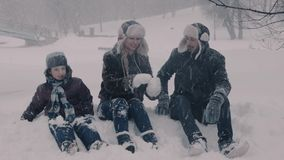 Family sitting on the snow. Two boys and there parents. Mama making snowballs. stock video