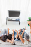 Family sitting on sofa cheering in front of television. At home Royalty Free Stock Photos