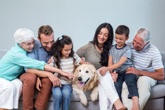 Family sitting on sofa with dog. In living room Royalty Free Stock Photos