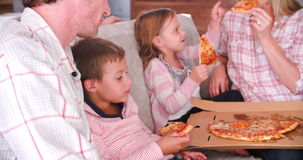 Family Sitting On Sofa Eating Takeaway Pizza Together