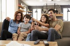 Family Sitting On Sofa In Open Plan Lounge Watching Television Stock Photo