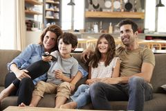 Family Sitting On Sofa In Open Plan Lounge Watching Television Royalty Free Stock Photos