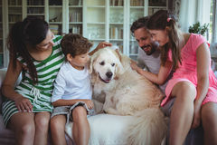 Family sitting on sofa with pet dog in living room Stock Photos
