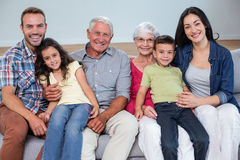 Family sitting on sofa. Portrait of family sitting on sofa and smiling in living room Stock Photography